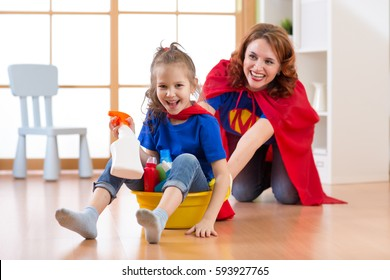 Preschooler child girl and her mother playing while doing cleanup at home