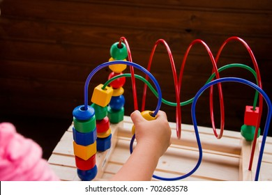 Preschooler child playing with colorful toy. Kid playing with educational wooden toys at kindergarten. Toddle in nursery room. Toy for the development of mental abilities, logical thinking.