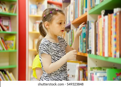 preschooler choosing books at   library.