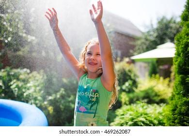 Preschooler cute girl playing with garden sprinkler. Summer outdoor water fun in the backyard