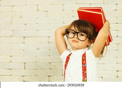 Preschooler girl with books on the head