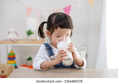 Preschooler girl drinking some milk with glass on sunny day, kindergarten or day care