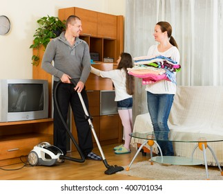 Preschooler girl helping parents to clean at living room. Focus on man