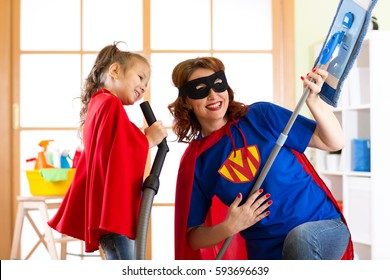 Preschooler girl and her mother dressed like superheroes. Middle-aged woman and child playing while doing cleanup at home