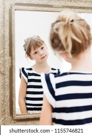 preschooler girl looking at herself in mirror. kid playing with reflection indoors. cute girl making faces to herself in the mirror
