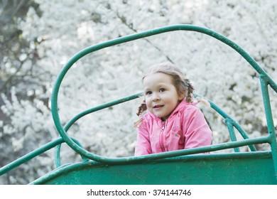 Preschooler girl on top of old vintage playground slide in spring blooming fruit trees park
