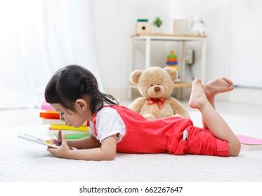 Preschooler girl playing tablet on carpet floor, Educational concept for school kids.