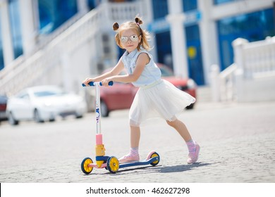 Preschooler girl riding scooter outdoors. Happy cute little child wearing blue safety helmet playing on the street learning to balance on kick board in the countryside