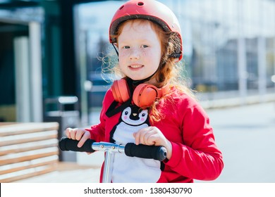 preschooler happy red hair girl with freckles holding roller outdoors. sunny spring day kid active leisure in town. cute child wearing protective orange helmet while riding scooter.
