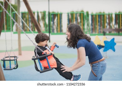 Preschooler having fun swinging at the park having fun with mother