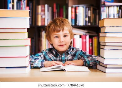 preschooler little boy reading a book in the library. the little boy with books near a bookcase