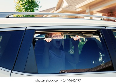 Preschooler little Caucasian girl left alone in car during hot sunny day. Child crying screaming trying to get out of closed vehicle at summer. Children safety protection kidnapping concept.