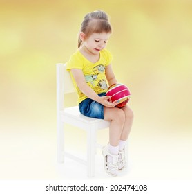 preschooler little girl sitting on a chair and holding the ball in front of him.passionate child for interesting occupation,active lifestyle,happiness concept,carefree childhood concept.