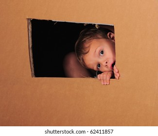 "A preschooler playing inside a large cardboard box with his brother.  He's peeking through a rough-cut ""window""."