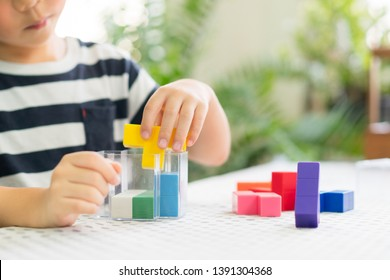 Preschooler plays colorful block puzzle. Child development - Hands-on activities developing problem solving skill, cognitive skill, concentration and emotional intelligence. Learn through play.