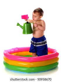 A preschooler pouring water from a plastic cup to a watering can while standing in a colorful kiddie pool.  Isolated on white.