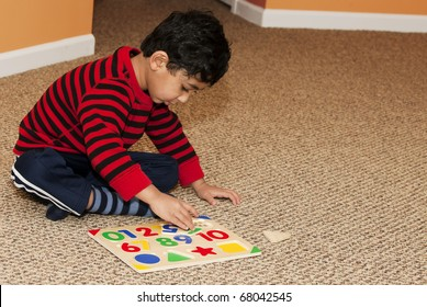 Preschooler Working On Numbers and Shapes Puzzle