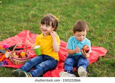 preschoolers - a girl in a yellow polo with a bang and a boy in a blue T-shirt are sitting on a red plaid and eating apples and drinking juice. children's picnic. Indian summer. horizontal photo
