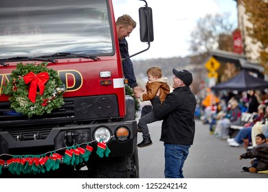 Prescott, Arizona, USA - December 1, 2018: Williamson Valley Fireman reaching to shake hands with young boy at the Christmas Parade