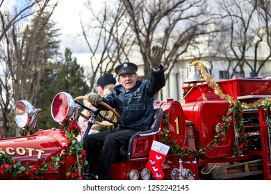Prescott, Arizona, USA - December 1, 2018: Fireman driving a firetruck waving while participating in the Christmas parade in downtown Prescott