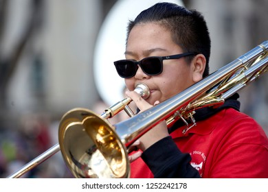 Prescott, Arizona, USA - December 1, 2018: Student from Mile High Middle School Band playing the trombone while marching in the Christmas parade in downtown Prescott