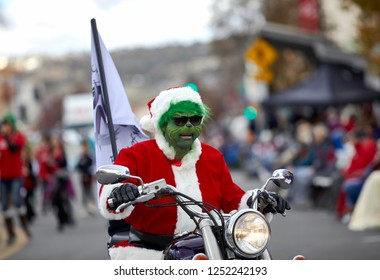 Prescott, Arizona, USA - December 1, 2018: Man wearing a Grinch Mask riding a motorcycle in the Christmas Parade on Cortez St.