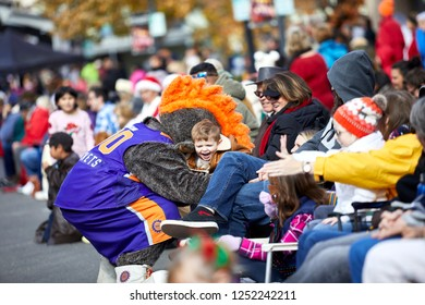 Prescott, Arizona, USA - December 1, 2018: Man wearing a bull costume with a basketball uniform hugging a young boy in the crowd while marching in the Christmas parade in downtown Prescott