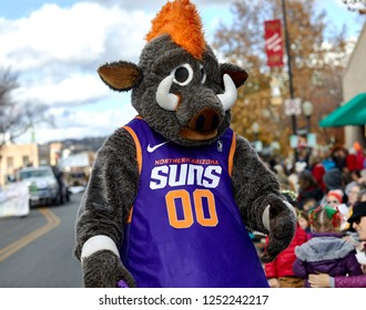 Prescott, Arizona, USA - December 1, 2018: Man wearing a bull costume with a Northern Arizona Suns basketball uniform while marching in the Christmas parade in downtown Prescott