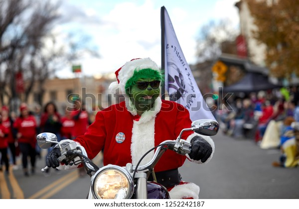 Prescott, Arizona, USA - December 1, 2018: Man wearing a Grinch mask with Santa costume riding a motorcycle in the Christmas parade in downtown Prescott