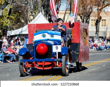 Prescott, Arizona, USA - November 10, 2018: Clown driving an antique truck that sprays out bubbles representing APS in the Veteran's Day Parade on Cortez St.