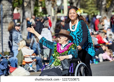Prescott, Arizona, USA - November 10, 2018: Elderly Veteran waving her hand while in a wheelchair being pushed by her daughter in the Veteran's Day Parade on Cortez St.