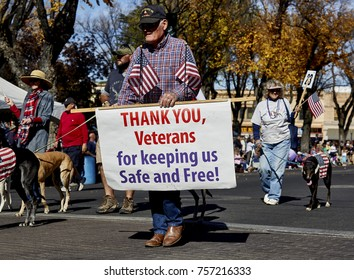 Prescott, Arizona, USA - November 11, 2017:Man holding sign while marching with the greyhound club in the Veterans Day Parade