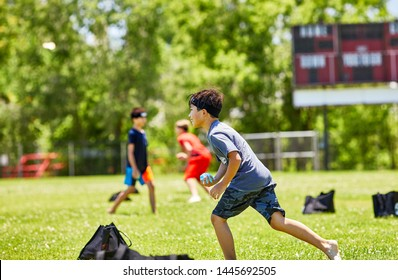 Prescott, Arizona, USA-July 6, 2019: Young boy preparing to throw a water balloon while running at the Water Wars event at Mile High Middle School field in downtown Prescott