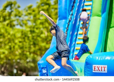Prescott, Arizona, USA-July 6, 2019: Young boy exiting an inflatable water slide at the Water Wars on the Mile High Middle School field in downtown Prescott