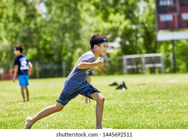 Prescott, Arizona, USA-July 6, 2019: Young boy preparing to throw a water balloon at the Water Wars event at Mile High Middle School field in downtown Prescott
