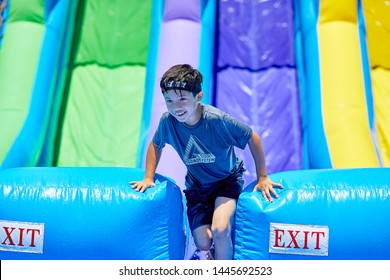 Prescott, Arizona, USA-July 6, 2019: Young boy exiting the water slide at the Water Wars on the Mile High Middle School field in downtown Prescott