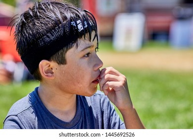 Prescott, Arizona, USA-July 6, 2019: Close up of a young boy resting after being on  an inflatable water slide at the Water Wars on the Mile High Middle School field in downtown Prescott