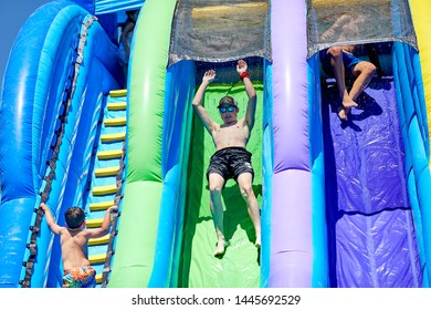 Prescott, Arizona, USA-July 6, 2019: Teenage boy sliding down an inflatable water slide at the Water Wars on the Mile High Middle School field in downtown Prescott
