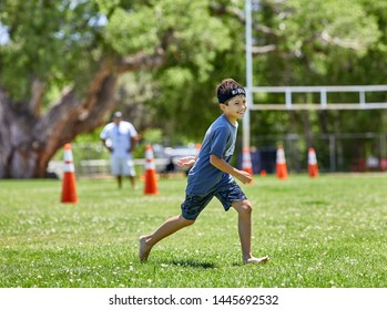 Prescott, Arizona, USA-July 6, 2019: Young boy running barefoot on a grass field at the Mile High Middle School field in downtown Prescott