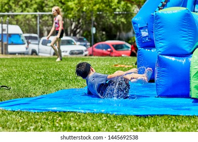 Prescott, Arizona, USA-July 6, 2019: Young boy sliding and falling upon exiting an inflatable water slide at the Water Wars on the Mile High Middle School field in downtown Prescott