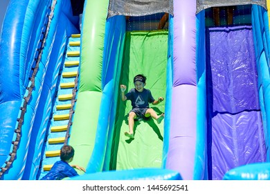 Prescott, Arizona, USA-July 6, 2019: Young boy sliding down an inflatable water slide at the Water Wars on the Mile High Middle School field in downtown Prescott