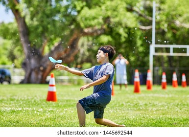 Prescott, Arizona, USA-July 6, 2019: Young boy throwing a water balloon at the Water Wars event at Mile High Middle School field in downtown Prescott