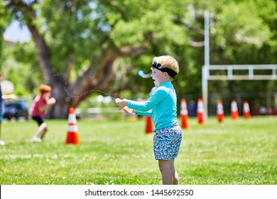 Prescott, Arizona, USA-July 6, 2019: Young girl squeezing water out of a water balloon at the Water Wars event at Mile High Middle School field in downtown Prescott