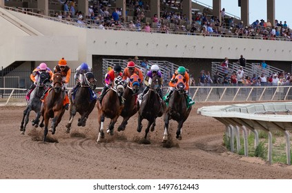 Prescott Valley, Arizona / USA - September 1, 2019. Horses and jockeys round the first bend on the racetrack at Arizona Downs. - Version 2