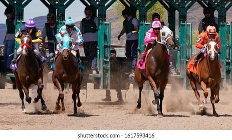 Prescott Valley, Arizona/USA - September 1, 2019 : Jockeys and Racehorses leave the gate and head down the stretch toward the camera.