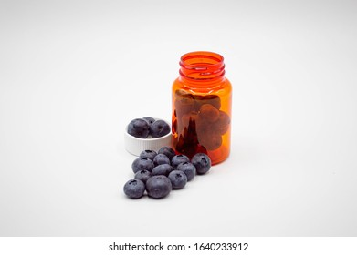 Prescription bottle with cap with fresh blueberries pouring out