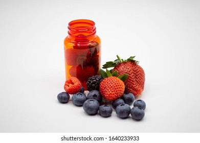 Prescription bottle with fresh strawberries, blueberries, raspberries, and blackberries spilling out