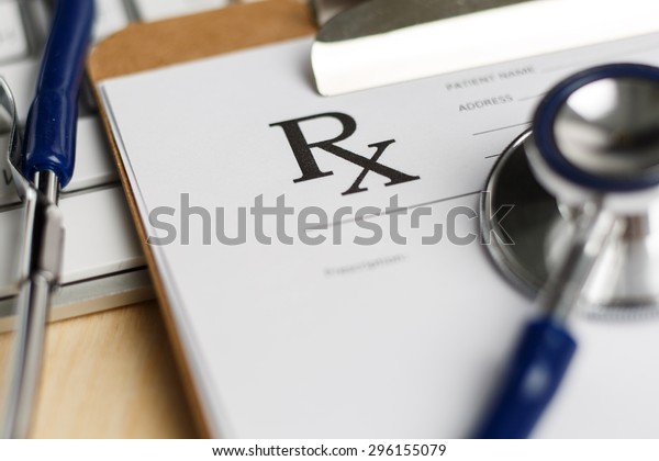Prescription form clipped to pad lying on table with keyboard and stethoscope. Medicine or pharmacy concept. Empty medical form ready to be used