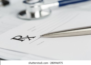 Prescription form lying on table with stethoscope and silver pen. Medicine or pharmacy concept. Empty medical form ready to be used.