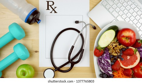 Prescription for good health overhead with stethoscope, healthy fresh food and exercise equipment.